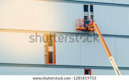 construction worker at construction site using lifting boom machinery