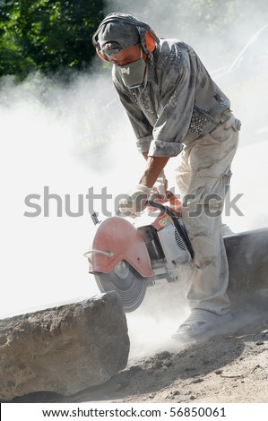 construction worker at stone cutting work by cut-off saw with diamond wheel
