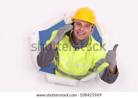 Construction worker breaking through a barrier and giving the thumb's up