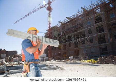 Construction worker carrying concrete beam