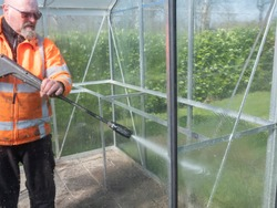 Construction worker cleaning filth with high pressure cleaner from a glass greenhouse.