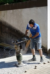 Construction worker compacting soil using compactor. Work with tamping machine