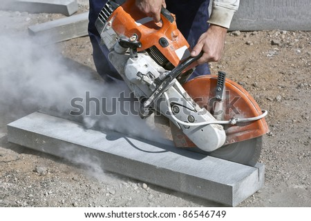 Construction worker cutting concrete curb