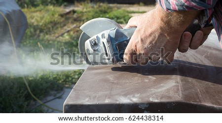 Construction worker cutting concrete plate for fence foundation using a cut-off saw.  #624438314