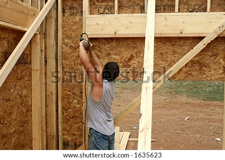 construction worker cutting out window on a new house