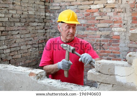 Construction worker demolishing old brick wall with chisel tool and hammer, real people