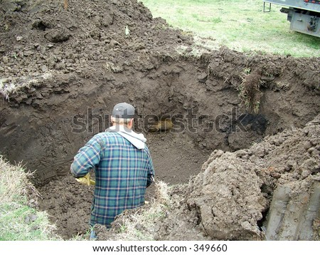 Construction worker digging a hole for a storm shelter