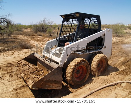 Construction worker driving a skid steer loader at a desert construction site. Horizontally framed shot.