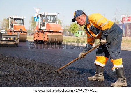 Construction Worker during Asphalting Road Works on Vibratory Rollers Machines background