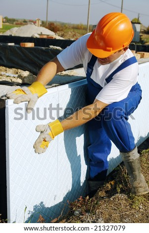 Construction worker fitting thermal insulation panels to house foundation walls