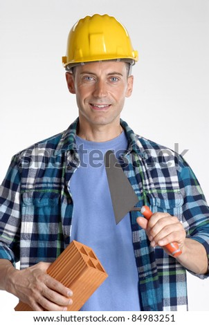 Construction worker holding a brick and trowel.
