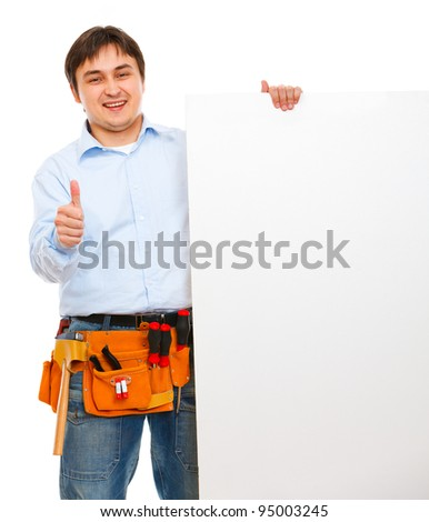 Construction worker holding blank billboard and showing thumbs up - stock photo