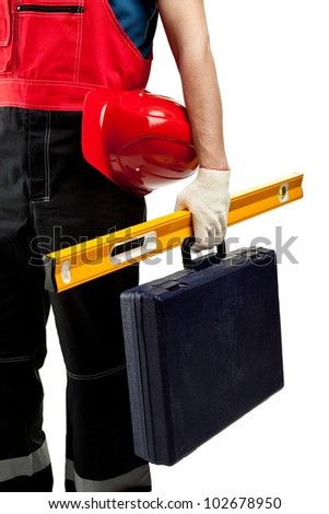 Construction worker holding hardhat, level and suitcase with special tools; isolated on white