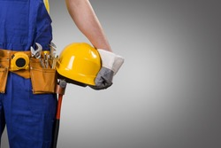 construction worker holding helmet on gray background with copy space
