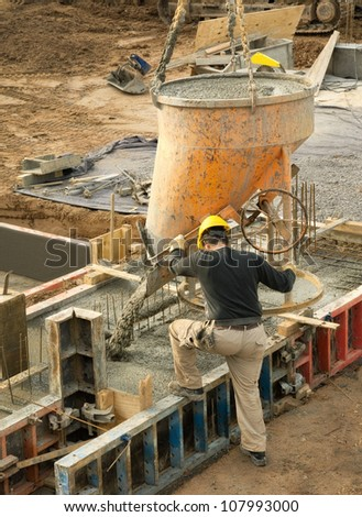 Construction worker in action: concrete being poured into the foundation