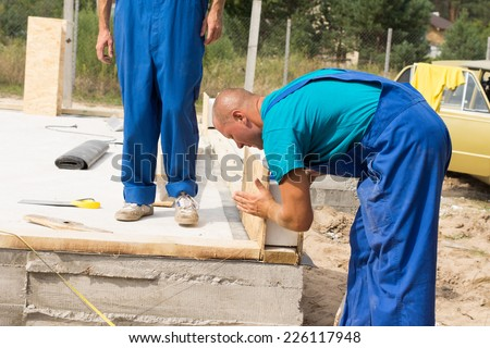 Construction worker in colorful blue overalls lining up insulated wooden wall panels on the foundation of a new build house watched by a co-worker