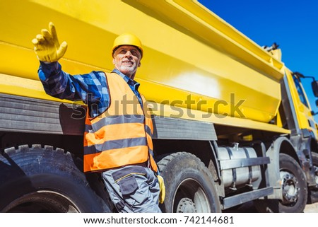 Construction worker in hardhat and reflective vest posing in front of yellow tip truck