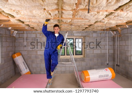 Construction worker in overalls fitting insulation into roof at camera