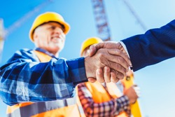 Construction worker in protective uniform shaking hands with businessman at construction site