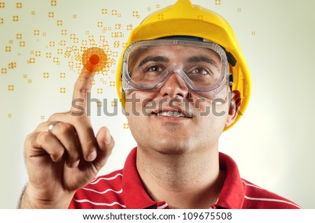 Construction worker in red shirt with hard hat pressing a touch screen with his index finger. Computer generated graphics - modern computer graphic interface for construction industry.