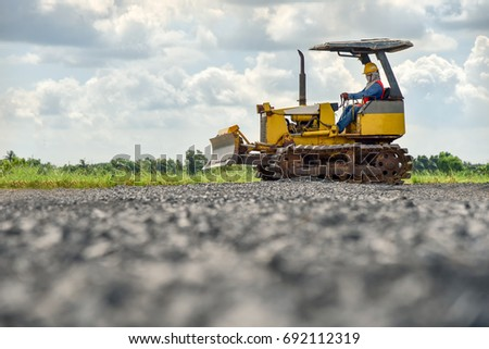 Construction worker in safety uniform driving grader tractor or construction machine move the soil in construction site and beautiful sky background