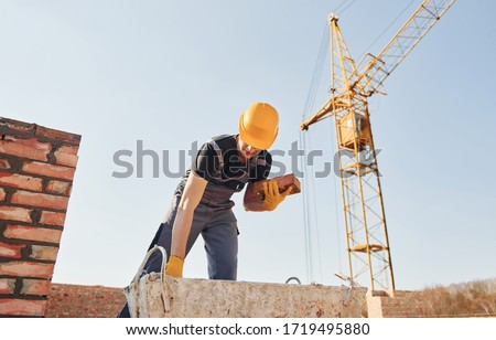 Construction worker in uniform and safety equipment have job on building.