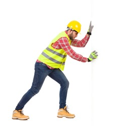 Construction worker in yellow helmet and reflective lime waistcoat pushing white wall. Full length studio shot isolated on white.