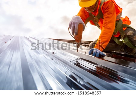 Construction worker install new roof,Roofing tools,Electric drill used on new roofs with Metal Sheet. ストックフォト ©