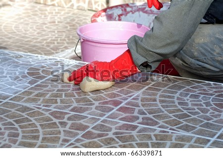 construction worker installing decorative tiles
