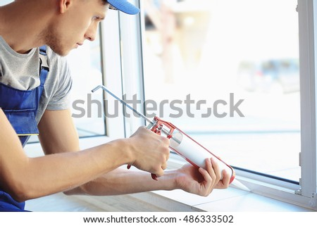 Construction worker installing window in house #486333502