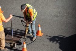 Construction worker jackhammering a city street, with space for text on the right