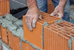 Construction worker laying hollow clay block at construction site