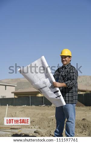 Construction worker looking blueprints