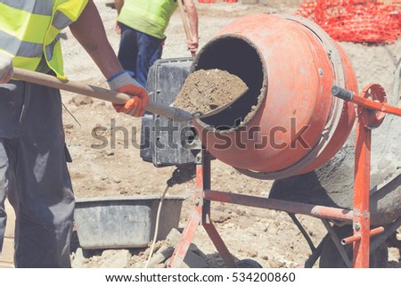 Construction worker making concrete in the mixer.