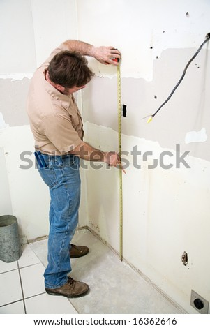 Construction worker measuring the wall during a kitchen remodeling job.  Authentic and accurate content depiction.