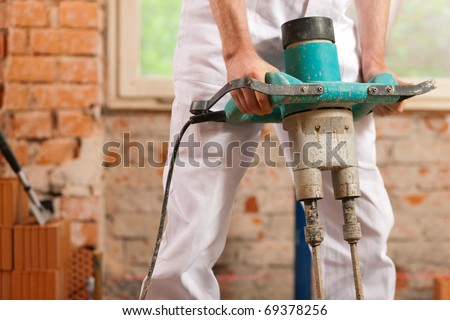 Construction worker mixing concrete or grout with a hand mixer