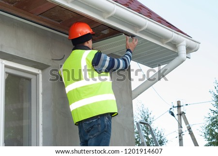 construction worker mounts a soffit on the roof eaves Stock photo ©
