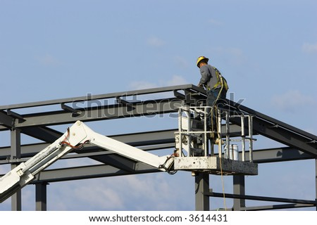 Construction worker on a cherry picker crane erecting a building at a site.