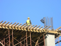 Construction worker on top of a residential building under construction, Tirana, Albania