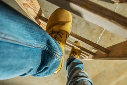 Construction Worker on Wooden Ladder. Shoes Closeup Photo.