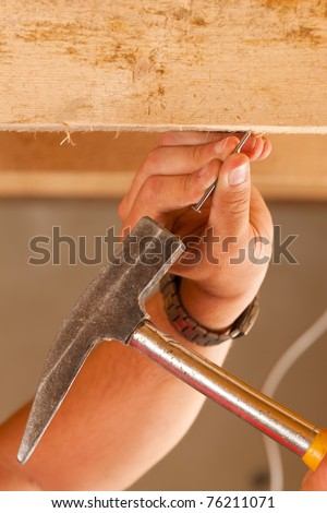Construction worker â?? only hand to be seen - with hammer and nail - stock photo