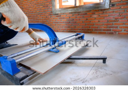 Construction worker or industrial tile worker Working on ceramic tile floor tile cutting equipment using ceramic cutter. Foto stock ©