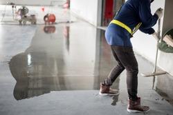 Construction worker painting epoxy flooring or floor hardener