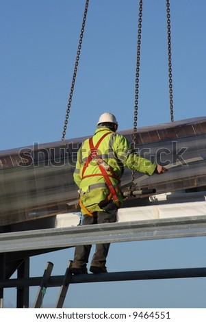 Construction worker perched on a metal structure.