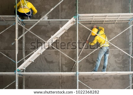 Construction worker plastering cement on concrete block wall