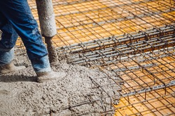 construction worker pouring cement or concrete with pump tube. Reinforced steel bars and rods