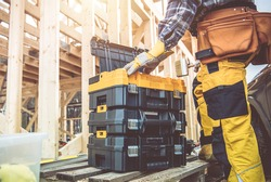 Construction Worker Preparing His Large Plastic Heavy Duty Toolboxes. Wooden Skeleton Frame of House in a Background. Construction Zone Theme.