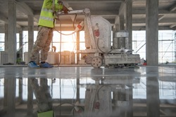Construction worker produces the grout and finish wet concrete with a special tool. Float blades. For smoothing and polishing concrete, concrete floors