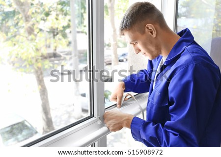 Construction worker putting sealing foam tape on window in house stock photo