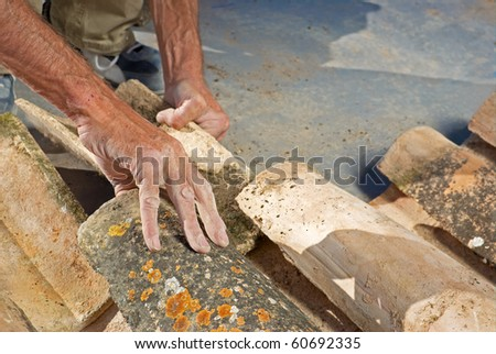 Construction worker repairing a roof with clay tiles